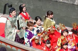 おひな様に扮したかわいい子供らが船でパレードします